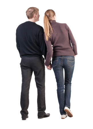 Back view of young couple (man and woman) hug and look into the distance. beautiful friendly girl and guy together. Rear view. Isolated over white background. husband and wife smiling coyly looking sideways