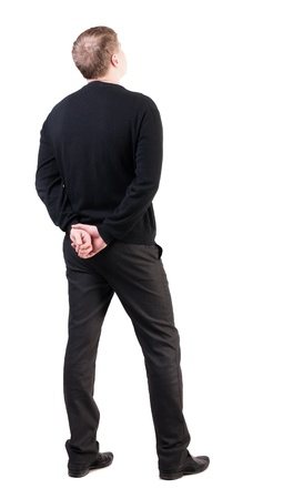 view from behind: back view of Business man  looks ahead. Young guy in sweater watching.  Rear view people collection.  backside view of person.  Isolated over white background. his hands clasped behind his back office worker looks at the sky