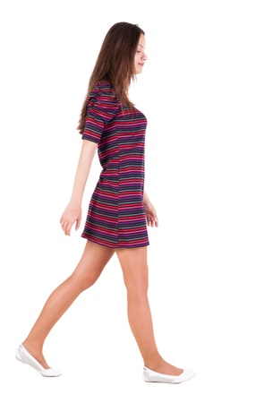 back view of walking  woman . beautiful brunette girl in motion.  backside view of person.  Rear view people collection. Isolated over white background. A smiling girl goes past us Imagens