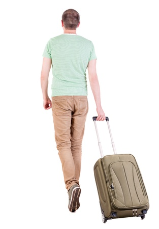back view of walking  man  with suitcase. brunette guy in motion. backside view of person. Rear view people collection. Isolated over white background. guy in sneakers and t-shirt rolls over a suitcase with clothes photo