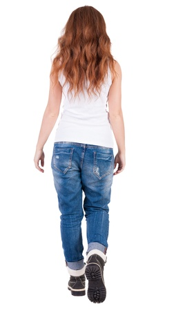 back view of walking  woman . beautiful redhead girl in motion.  backside view of person.  Rear view people collection. Isolated over white background. trendy teen girl goes in mountain boots and jeans photo