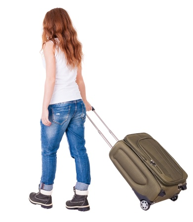 back view of walking  woman  with suitcase. beautiful redhead girl in motion.backside view of person. Rear view people collection. Isolated over white background. stylish girl in mountain boots and jeans roll travel bag photo