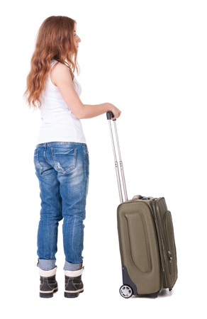 Back view of stylishly dressed woman with suitcase looking up. Standing young girl . Rear view people collection.  backside view of person. Isolated over white background. Sad girl in jeans and boots mountain is a tourist bag photo