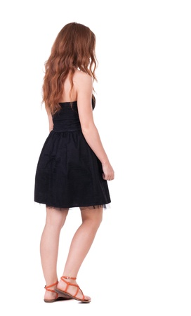 back view of walking young beautiful  redhead woman. girl  watching. Rear view people collection.  backside view of person.  Isolated over white background. red-haired girl in a black dress stepping aside photo