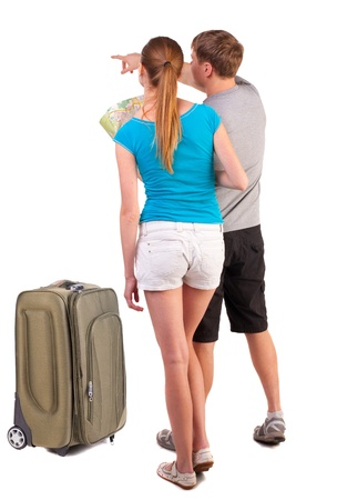Back view journey of the young couple with suitcase looking at map. Isolated over white background.  photo