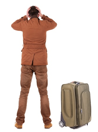 Back view of shocked business man with suitcase looking up. Isolated over white background. upset businessman photo