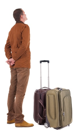 望ましく男を見上げてスーツケースと一緒に旅行の背面図です。若い男のジーンズやジャケットに立っています。白い背景の上に孤立しました。