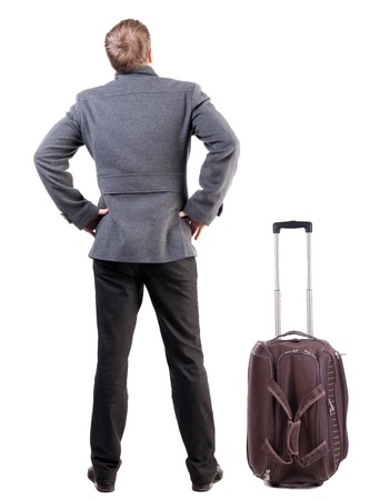 Back view of traveling busness man with  suitcase looking up. Standing young guy in jeans and  jacket.  Isolated over white background. photo