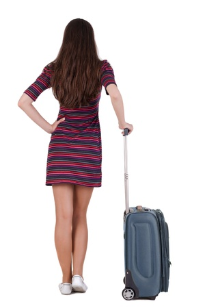 Back view of brunette woman with suitcase looking up. Isolated over white background. Pretty girl in a striped dress stands with a suitcase and looking at something photo