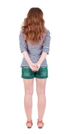 back view of standing young beautiful  redhead woman.  Isolated over white background. Red-haired teen in shorts and sandals is exactly photo