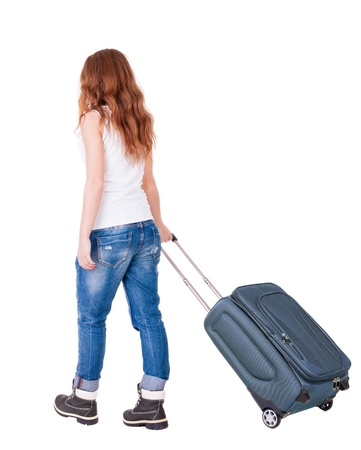 back view of walking  woman  with suitcase. Isolated over white background.  photo