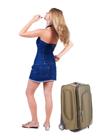 Back view of traveling blonde woman in dress with suitcase looking up. Standing young girl. Rear view people collection.  backside view of person. Isolated over white background. resting his hand on hip girl thoughtfully looks forward photo