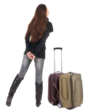 Back view of traveling brunette woman in jeans with suitcase looking up. Standing young girl. Rear view people collection.  backside view of person. Isolated over white background. resting his hand on hip girl thoughtfully looks forward photo