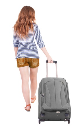 back view of walking  woman  with suitcase. beautiful redhead girl in motion.  backside view of person.  Rear view people collection. Isolated over white background. Red-haired beauty rolls for a carry-on bag photo