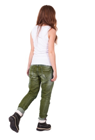 back view of walking  woman . beautiful redhead girl in motion.  backside view of person.  Rear view people collection. Isolated over white background. Stylish teenage girl in boots and vest goes forward. photo