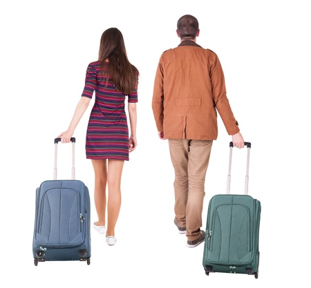 back view of walking  couple  with suitcase. pair in motion.  backside view of person.  Rear view people collection. Isolated over white background. photo