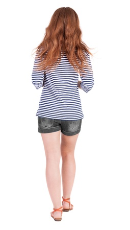 back view of walking young beautiful  redhead woman. girl  watching. Rear view people collection.  backside view of person.  Isolated over white background. by summer red-haired girl dressed in sandals goes ahead photo