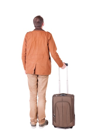 stylishly: Back view of stylishly dressed man in a brown jackett with  green suitcase looking up.   Standing young guy in jeans and  jacket. Rear view people collection.  backside view of person.  Isolated over white background. Stock Photo