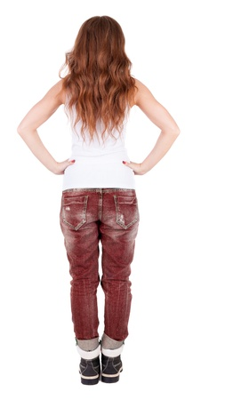 back view of standing young beautiful  woman. girl  watching. Rear view people collection.  backside view of person.  Isolated over white background. girl in a white T-shirt stands with his hands on waist photo