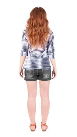 back view of standing young beautiful  redhead woman. girl  watching. Rear view people collection.  backside view of person.  Isolated over white background. Red-haired teen in shorts and sandals is exactly photo