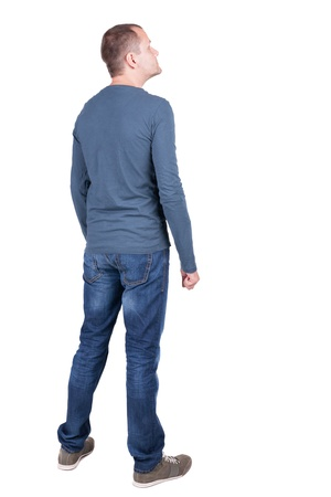 looking behind: Back view of young man in t-shirt and jeans  looking.   Standing young guy. Rear view people collection.  backside view of person.  Isolated over white background.