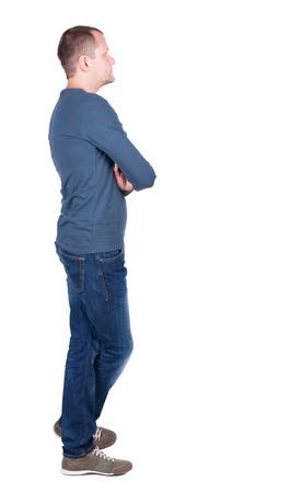 persona: Volver la vista de joven en camiseta y pantalones vaqueros mirando. De pie chico joven. Vista posterior recogida de las personas. trasero vista de la persona. Aislado sobre fondo blanco.