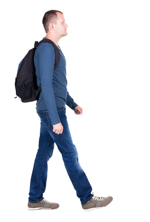 back view of walking  man  with backpack.  brunette guy in motion. backside view of person.  Rear view people collection. Isolated over white background. young man goes to side of a rolling travel bag on wheels Standard-Bild