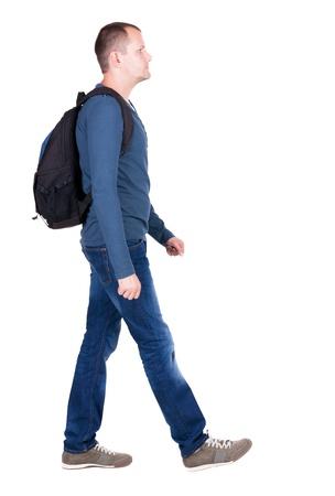 mochila viaje: Vista posterior de la marcha del hombre con mochila. chico morena en marcha. trasero vista de la persona. Vista posterior recogida de las personas. Aislado sobre fondo blanco. joven va al lado de una bolsa de viaje de rodadura con ruedas