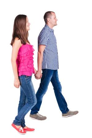 parejas caminando: Vista posterior de caminar joven pareja (hombre y mujer). va hermosa chica y un chico agradable juntos. Vista posterior recogida de las personas. trasero vista de la persona. Aislado sobre fondo blanco