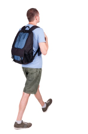 back view of walking  man  with backpack.  brunette guy in motion. backside view of person.  Rear view people collection. Isolated over white background. young man goes to side of a rolling travel bag on wheels photo