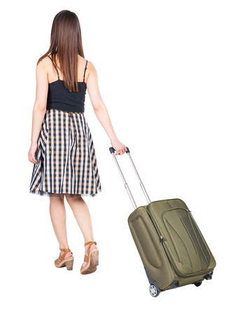 back view of walking woman  with green suitcase. beautiful brunette girl in motion.  backside view of person.  Rear view people collection. Isolated over white background. girl on the heels of a suitcase rolls photo