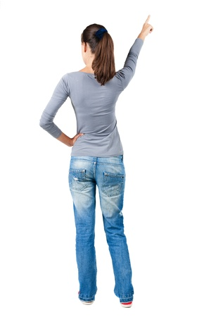backview: Back view of  pointing woman. beautiful brunette  girl in jeans.  Rear view people collection.  backside view of person.  Isolated over white background.