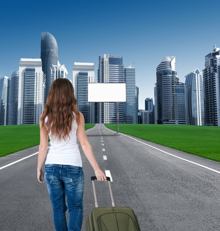 woman walking on the road to the city, in front of an empty Billboards. concept. tourist returns home to the city. moving to the city. billboard on the road leading to the city of skyscrapers. back view. photo
