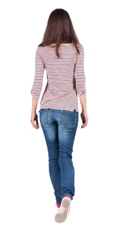 back view of walking  woman in jeans . beautiful brunette girl in motion.  backside view of person.  Rear view people collection. Isolated over white background. The girl in a striped T-shirt with sleeves podkatannymi goes ahead photo