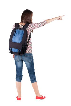 Back view of  pointing woman with backpack looking up. Standing young girl. Rear view people collection.  backside view of person. Isolated over white background. Pretty girl in a striped dress stands with a suitcase and looking at something photo