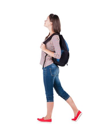 back view of standing young beautiful  brunette woman with backpack. traveling girl  watching. Rear view people collection.  backside view of person.  Isolated over white background.  photo