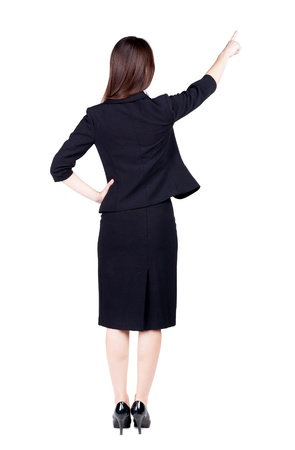 Back view of young brunette business woman pointing at wall. beautiful girl in dark suit. Rear view people collection. backside view of person. Isolated over white background. photo
