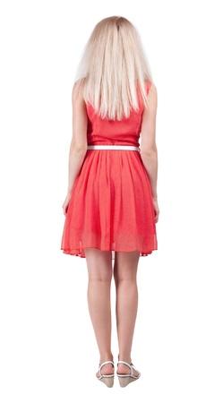 zurück zu stehen junge schöne Frau zu sehen. blonde Mädchen im roten Kleid und Kitten Heels beobachten. Rückansicht Menschen Kollektion. Rückansicht der Person. Isolierte über weißem Hintergrund. Standard-Bild