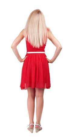 back view of standing young beautiful  woman. blonde girl in red dress and  kitten heels watching. Rear view people collection.  backside view of person.  Isolated over white background. photo