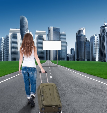 woman walking on the road to the city, in front of an empty Billboards. photo
