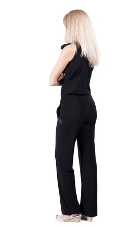 back view of standing young beautiful  blonde woman. she shyly looks at something. girl  watching. Rear view people collection.  backside view of person.  Isolated over white background. photo