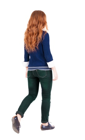 back view of walking  woman . beautiful redhead girl in motion.  backside view of person.  Rear view people collection. Isolated over white background. A girl in a blue sweater and a white shirt is moving forward photo