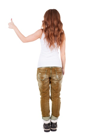 Back view of  woman thumbs up.   Rear view people collection.  backside view of person.  Isolated over white background. gesture demonstrated by the success of the stylish girl in a vest and mountain boots photo