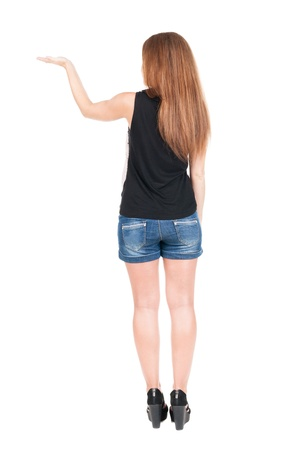 back view of surprised beautiful  young redhead woman with hands up. Girl in blue shotrs. Rear view. Isolated over white  photo