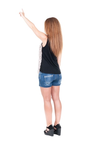 Back view of  pointing woman. beautiful redhead girl in shorts. Rear view people collection.  backside view of person.  Isolated over white background. photo