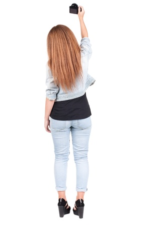 Back view of woman photographing. girl photographer in jeans. Rear view people collection.  backside view of person.  Isolated over white background. photo