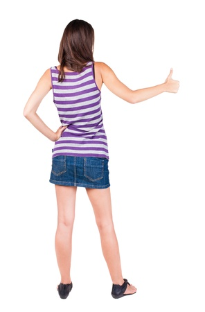 Back view of  woman thumbs up. Rear view people collection. backside view of person. Isolated over white background. slender brunette in a dress shows the symbol of success or hitchhiking photo