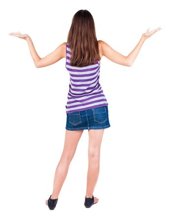 back view of surprised beautiful brunette young woman with hands up. Girl in blue dress. Rear view people collection.  backside view of person.  Isolated over white background. Stock Photo - 21647025