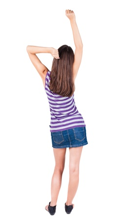 back view of standing young beautiful brunette woman thumbs up.  girl shows ok sign. Rear view people collection. backside view of person. Isolated over white background.  photo