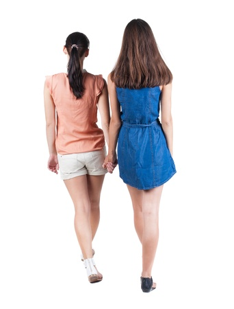 Back view going of two young  woman. Rear view people collection. backside view of person. beautiful girl friends walking.  Isolated over white background.  photo
